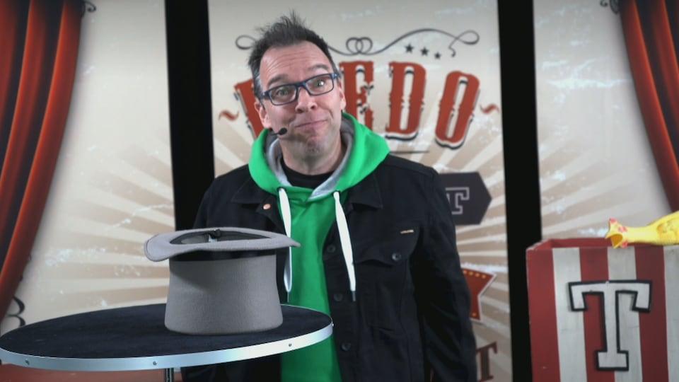 Un magicien se tient debout devant une table sur laquelle est posée un chapeau.
