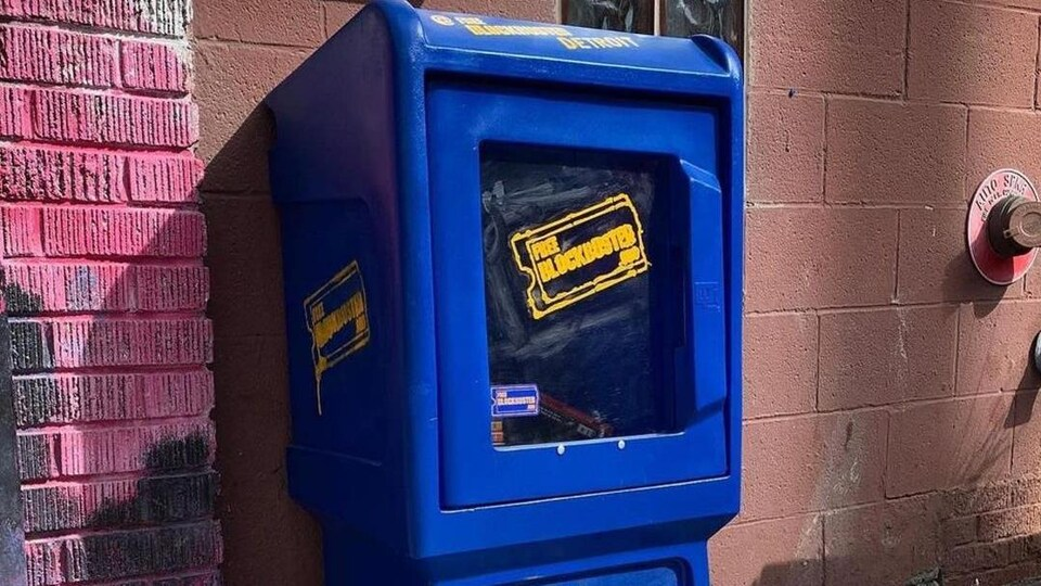 Une boîte bleue ressemblant à une distributrice à journaux avec le logo de Blockbuster.