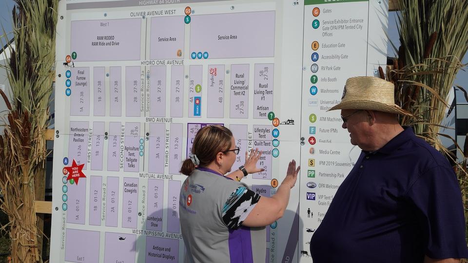 Un homme se fait donner des indications par Lise Goupil sur une carte.