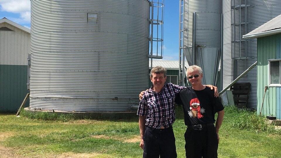 Les frères Parenteau au lendemain de leur aventure, Richard et Raymond devant le fameux silo à grains.