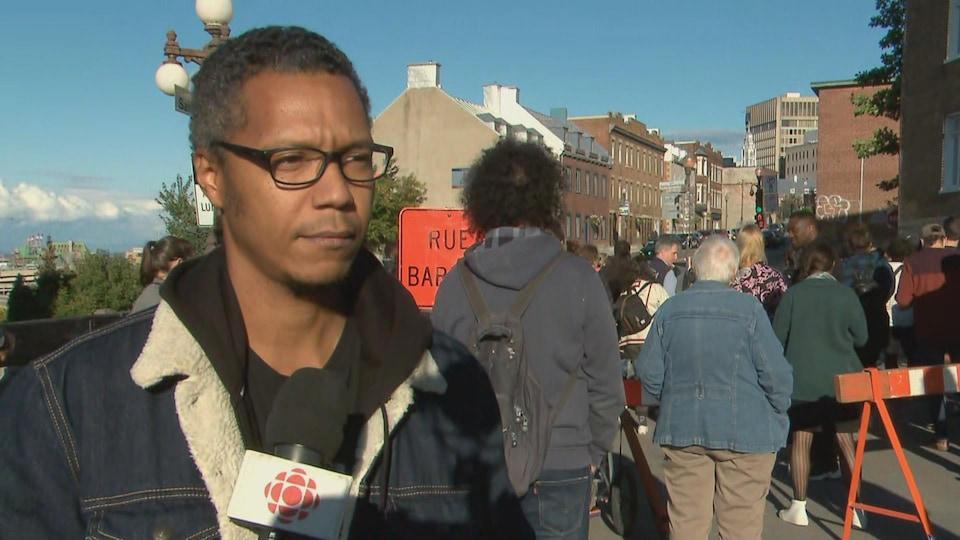 Un homme en entrevue à Radio-Canada, à l'extérieur. Un micro est pointé en direction de son visage.