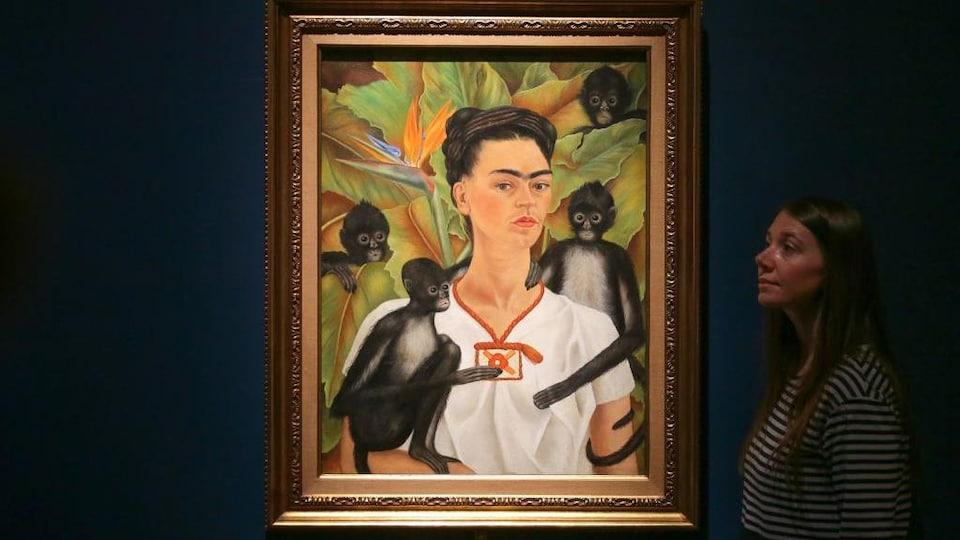 Le tableau, exposé sur un fond bleu, représente Frida Kahlo entourée de quatre petits singes noirs.