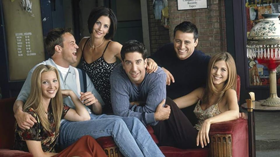 Les six acteurs et actrices de la série posent dans un appartement.
