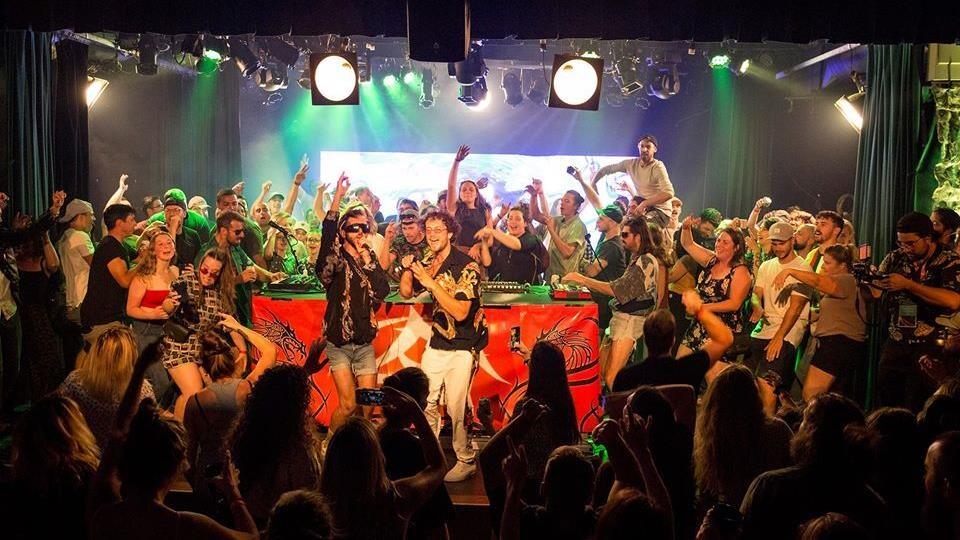 Une foule entoure des musiciens qui donnent un spectacle dans une salle.