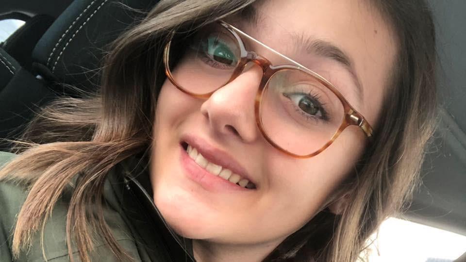 La jeune femme s'est prise en photo dans une voiture. Elle porte des lunettes.