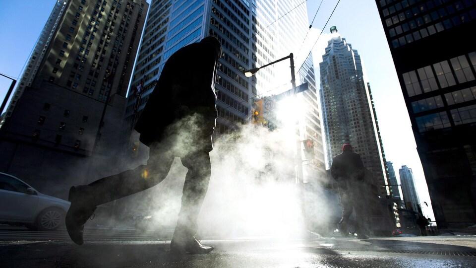 Un homme marche devant les gratte-ciels du quartier financier de Toronto.