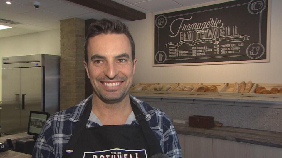 Un homme en tablier sourit, derrière lui il y a du pain sur une étagère.