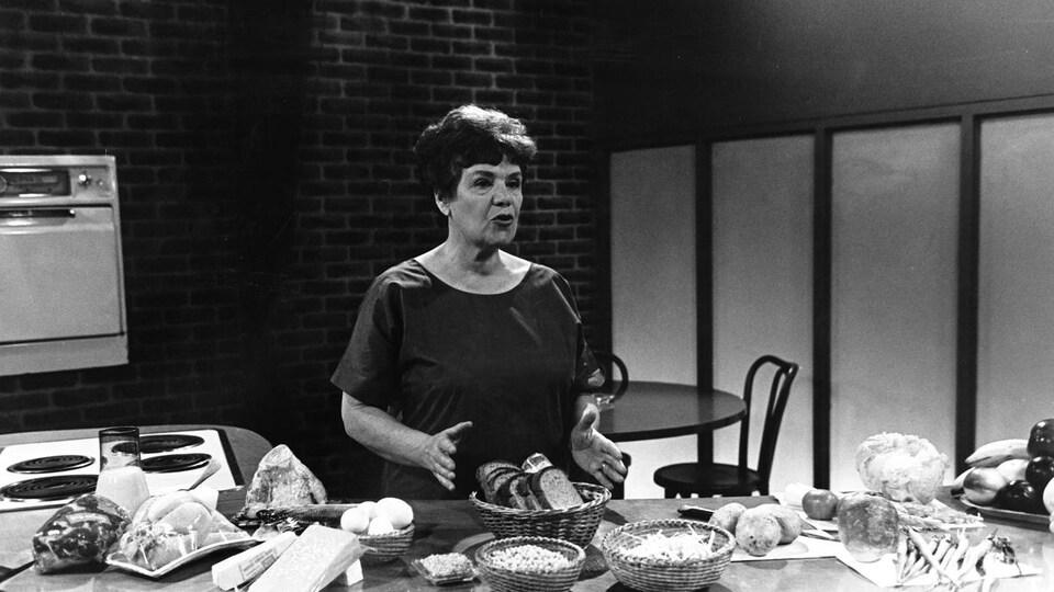 Dans un studio de télévision, la cuisinière Jehane Benoit, debout derrière un comptoir de cuisine, présente divers aliments, dont des fromages, du pain et des légumes.