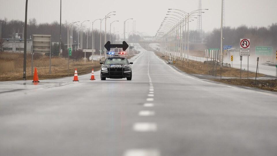 Une voiture de police est seule sur la longue route menant vers la frontière américaine.