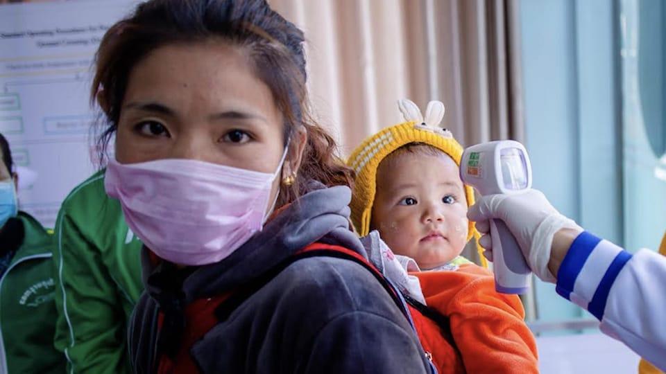 Une femme et son bébé lors d'un test médical où quelqu'un prend la température de l'enfant.