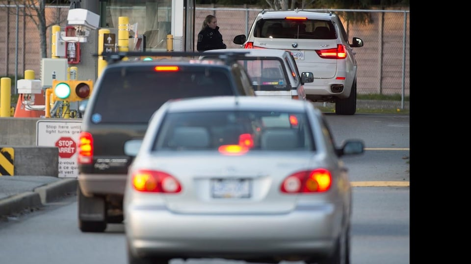 Des voitures s'enfilent à un poste frontalier entre les États-Unis et le Canada.