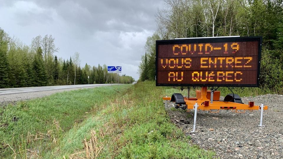 Une affiche lumineuse du MTQ indique «COVID-19 vous entrez au Québec».