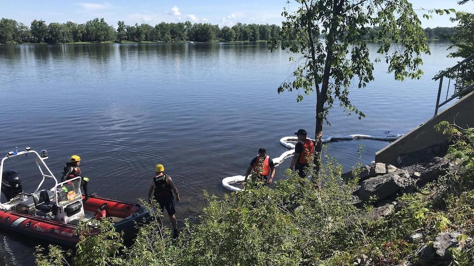 Des pompiers sur la rive de la rivière des Outaouais.