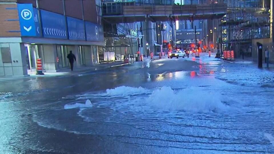 De l'eau jaillit du sol dans la rue.