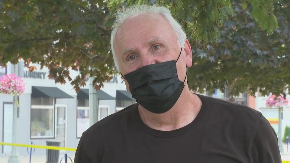 Un homme aux cheveux blancs parle devant la caméra.