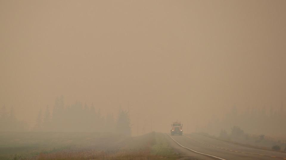 Un camion roule sur l'autoroute 27 dans un épais nuage de fumée entre Vanderhoof et Fort St. James