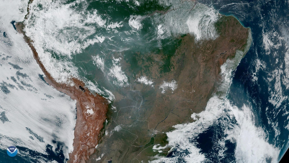 Une vaste portion de l'Amérique du Sud, partiellement recouverte de nuages et de fumée.