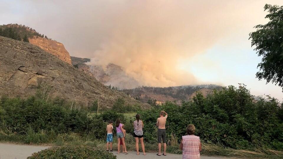 Des gens regardent la fumée s'étendre dans le ciel, au-dessus des flammes.