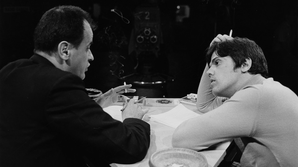 Dans un studio de télévision, l'invité Jean-Paul Desbiens (Frère Untel) parle, alors que l'animateur Guy Boucher l'écoute attentivement. Tous les deux ont une cigarette à la main. Entre les deux, on aperçoit le caméraman derrière sa caméra qui capte la scène.