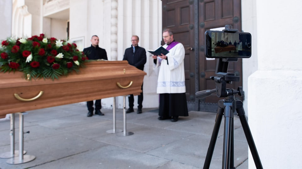 Un prêtre parle devant une tombe en étant filmé par un téléphone cellulaire sur trépied.