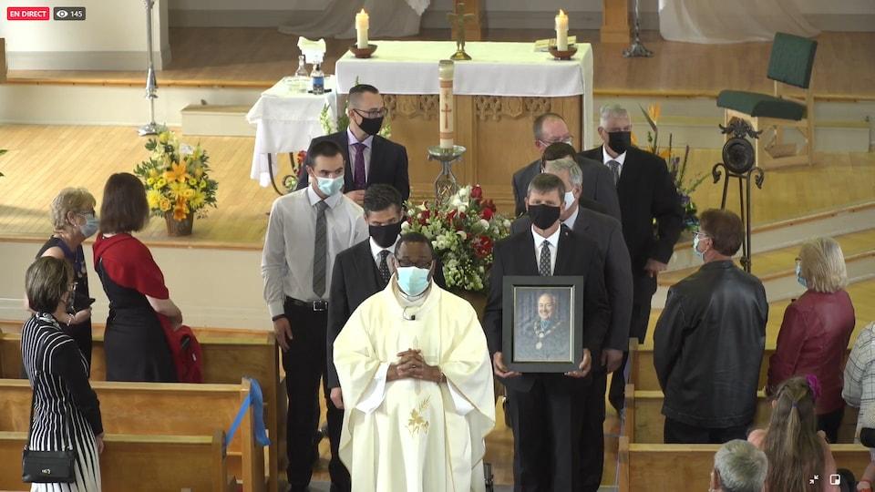 Un groupe d'homme autour du cercueil devant l'autel de l'église. Le prêtre se trouve devant le cercueil.