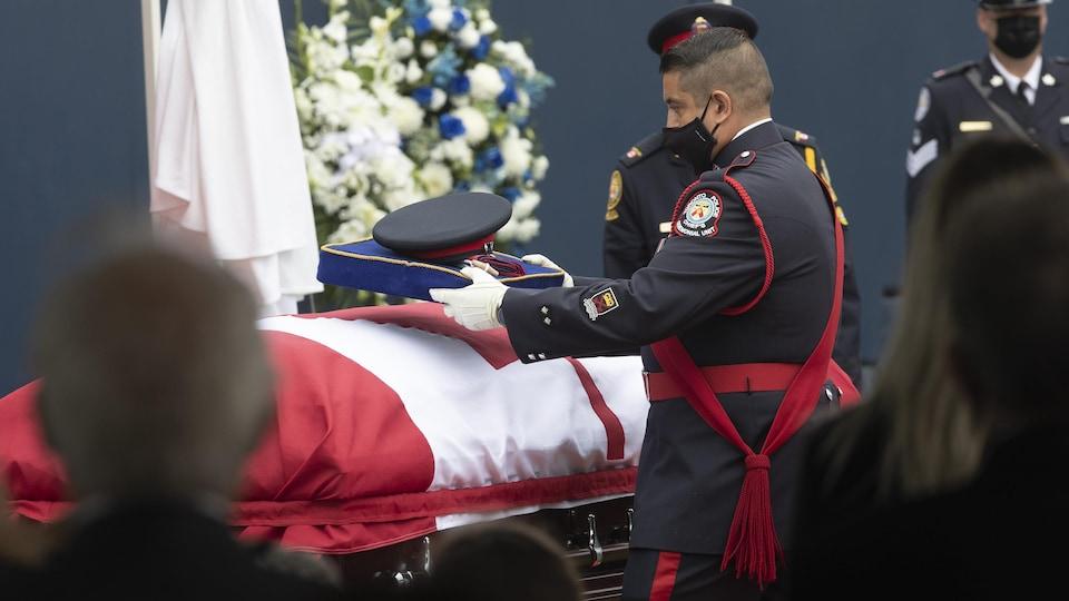 Un homme devant un cercueil couvert d'un drapeau canadien.