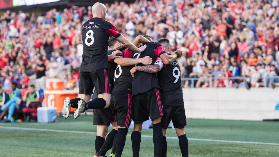 Les joueurs de soccer se sautent dans les bras devant les estrades d'un stade.