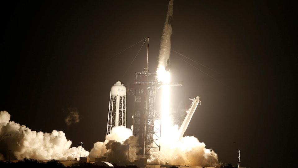 Des flammes et de la fumée sortent de la fusée.