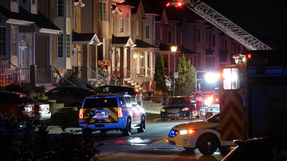 Des véhicules des pompiers et de la police dans un quartier résidentiel.