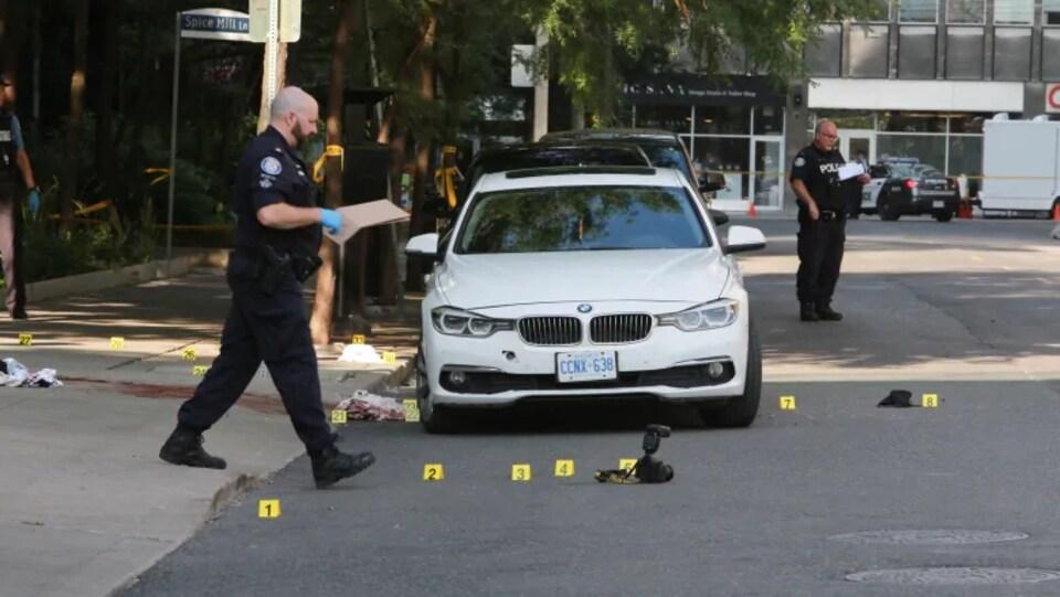 Photo de deux policiers debout dans la rue près d'une voiture BMW blanche entourée au sol de petits cartons jaunes numérotés montrant des balles.