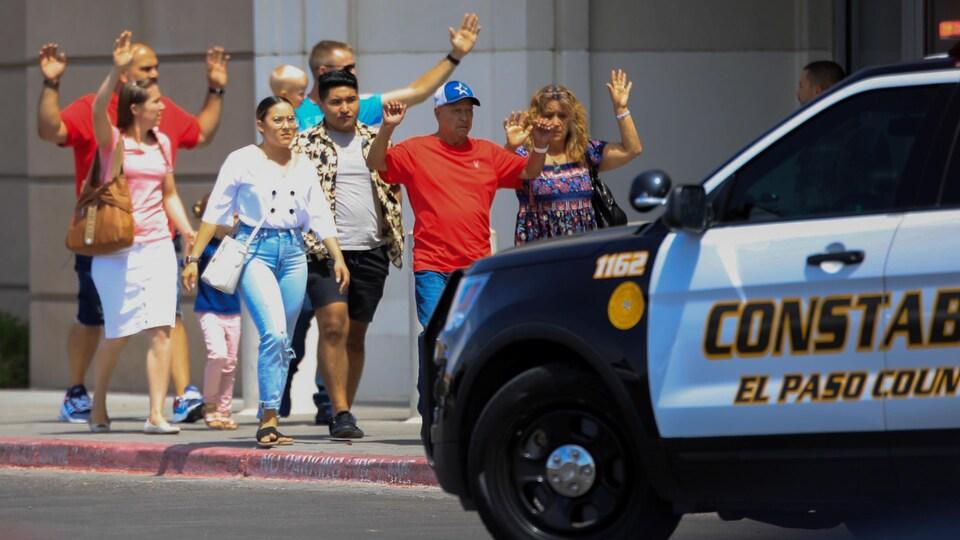 Des hommes et des femmes sortent d'un centre commercial en levant les mains en l'air devant une voiture de police.