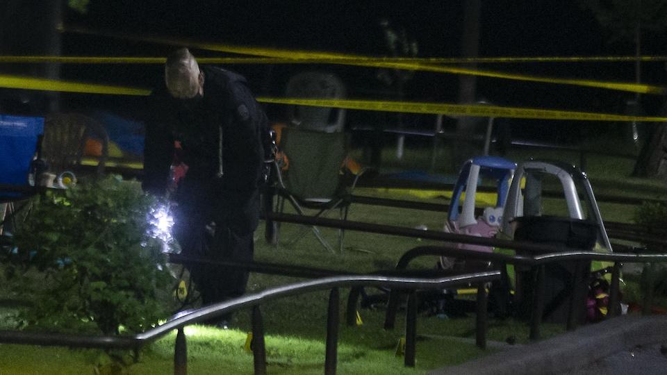 Un policier cherche des indices avec une lampe de poche à côté de jeux d'enfants.
