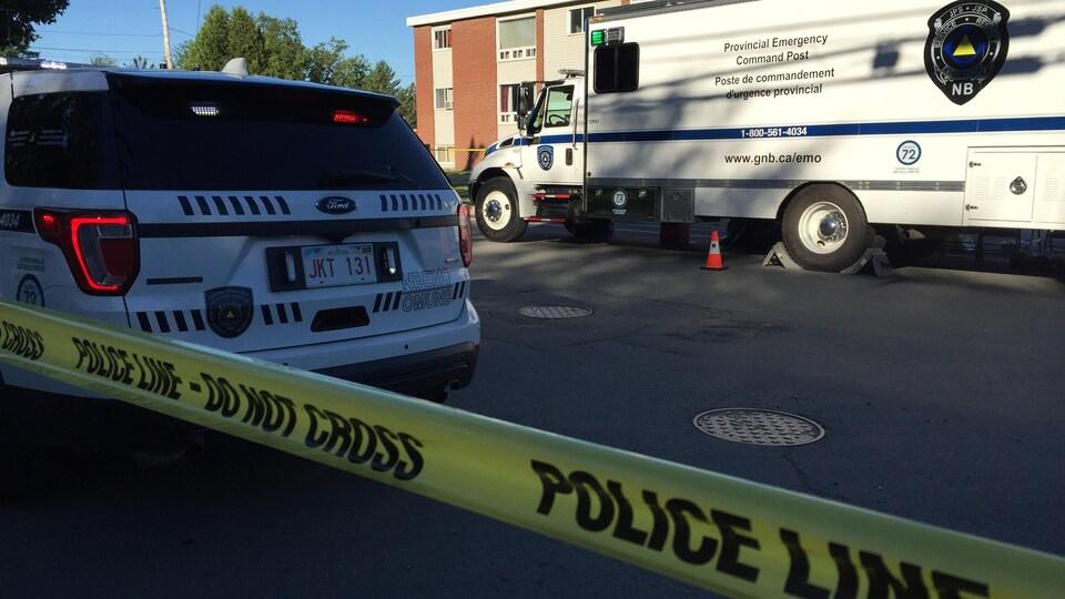 Derrière une bande jaune à ne pas franchir sont stationnés un véhicule et un camion des forces policières de Fredericton.