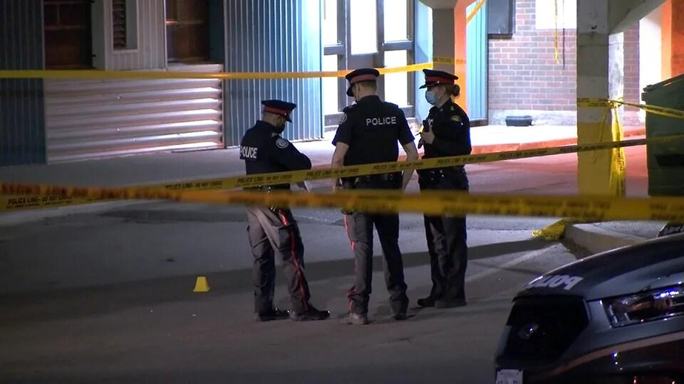 Trois policiers examinent le sol sur une scène de crime.