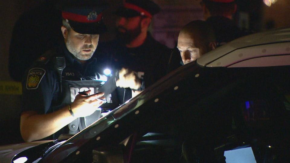 Un policier prend des notes devant une automobile.
