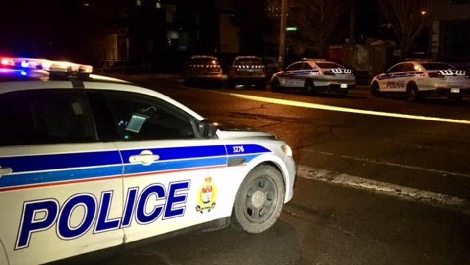 Cinq voitures de la police d'Ottawa à l'intersection d'une rue la nuit.