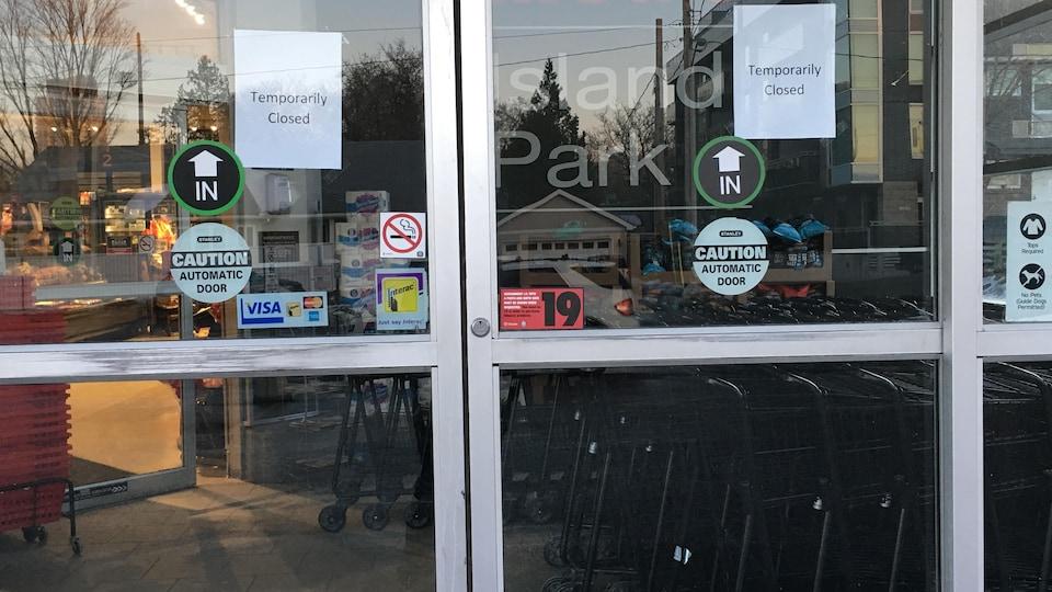 Une affiche annonçant la fermeture temporaire du commerce est collée sur la porte d'entrée.