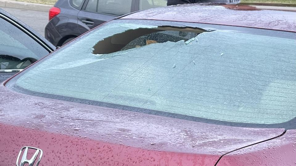 Un grand trou dans le pare-brise arrière d'une voiture bourgogne.