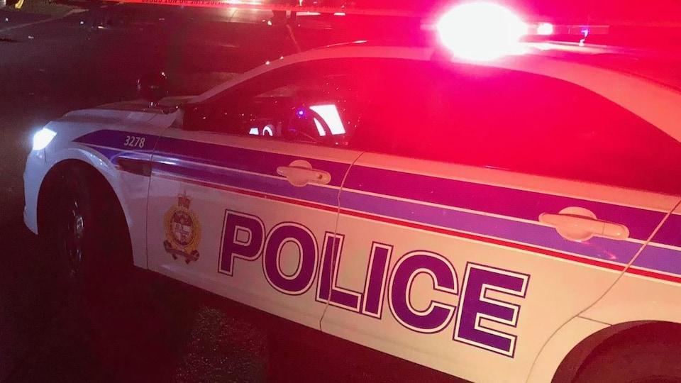 Des voitures de police avec les gyrophares allumés devant un périmètre de sécurité