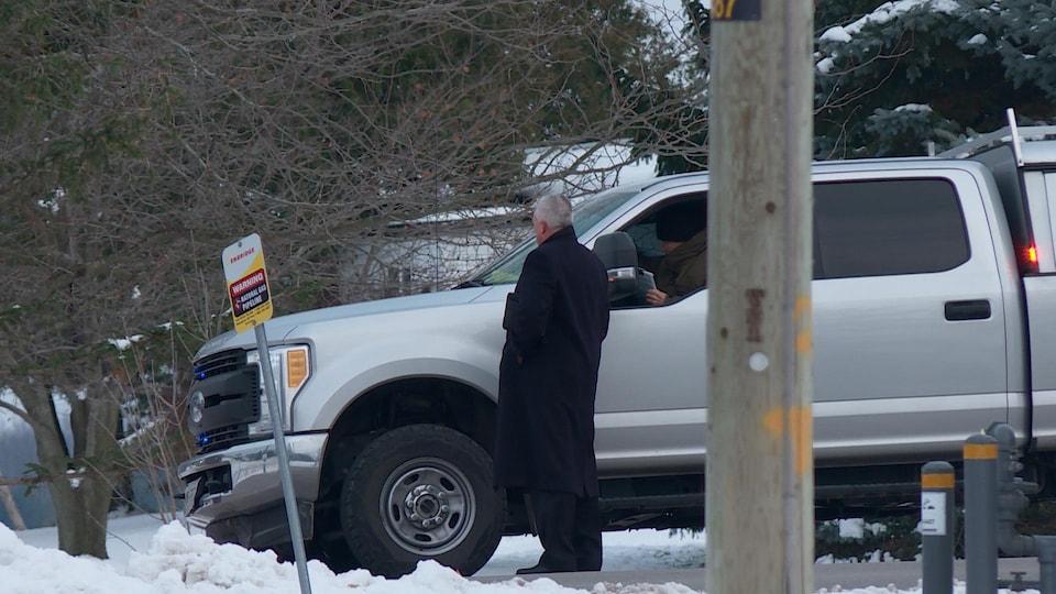 Un homme debout près de camion de type pick up. Il tient ce qui semble être un dossier ou un iPad. Paysage rural et hivernal autour de lui.