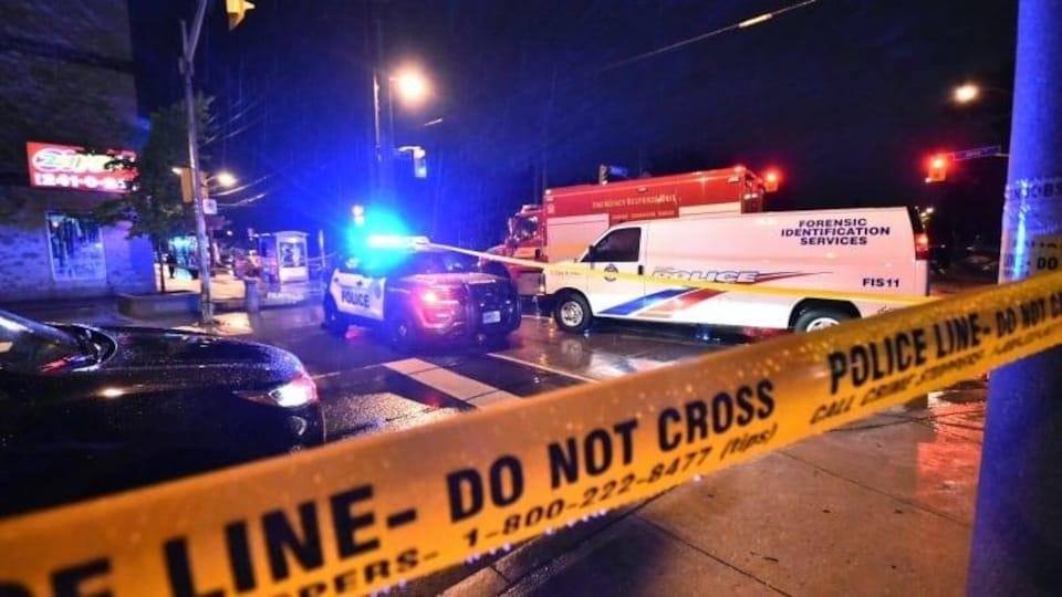 Une scène de crime, la nuit, entourée de ruban jaune de police. Plusieurs véhicules d'urgence sont sur place.