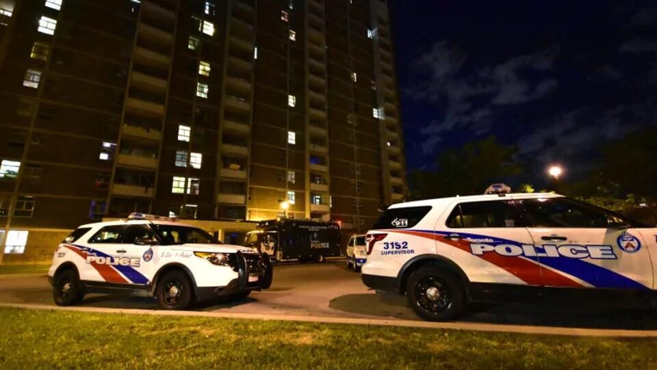 Photo de deux véhicules de police blancs, bleus et rouges stationnés devant un immeuble en briques de plusieurs étages, le soir.