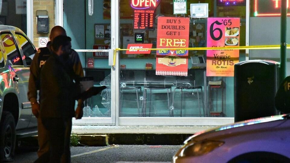 Des policiers sont devant la vitrine du commerce qui a reçu des impacts de balles.