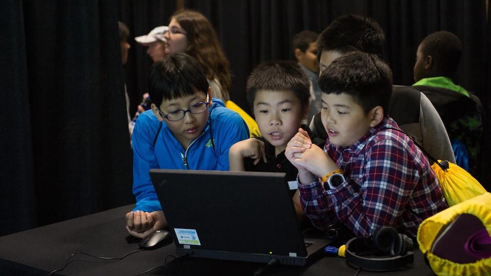 Trois garçons regardent avec attention un ordinateur dans une pièce sombre.