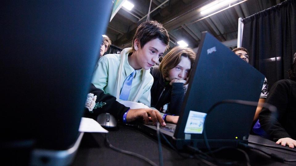 Deux jeunes jouent à un jeu sur un ordinateur.