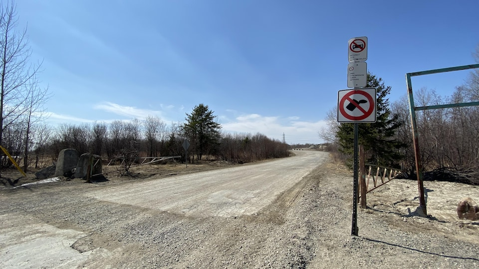Une affiche à l'entrée d'un chemin de gravier.