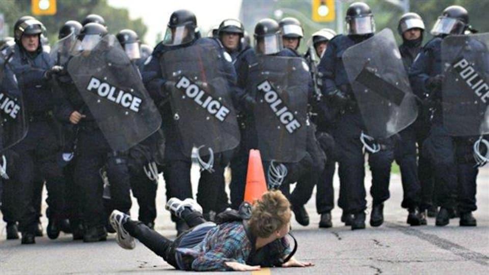 Le protestataire est couché sur le ventre, avec derrière lui un mur de policiers en marche.