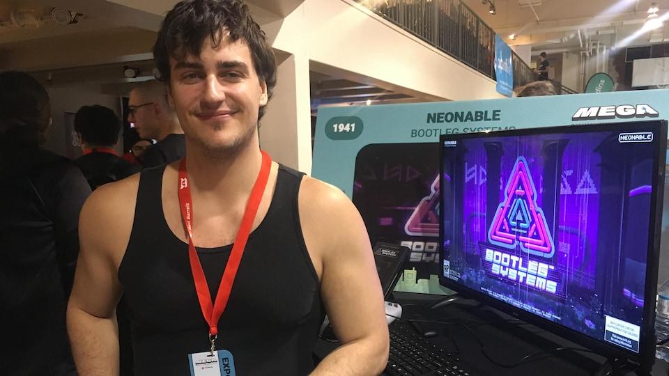 Un homme en camisole noir regarde la caméra en souriant. Il a le bras appuyé sur un bureau sur lequel se trouve un écran sur lequel est affiché le logo d'un jeu vidéo.