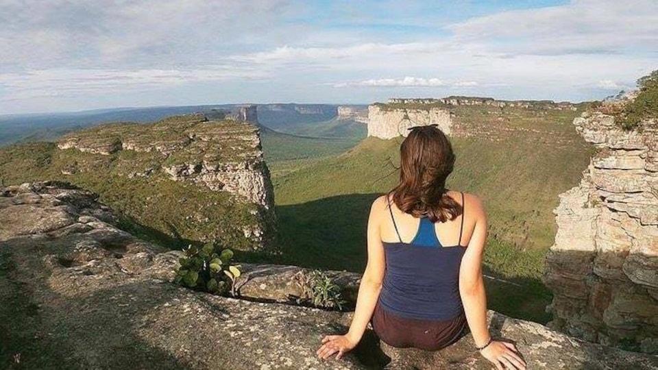 Une femme sur le bord d'une roche avec une vue panoramique.