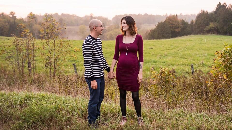 Un homme et une femme enceinte se tiennent par la main devant un champ.